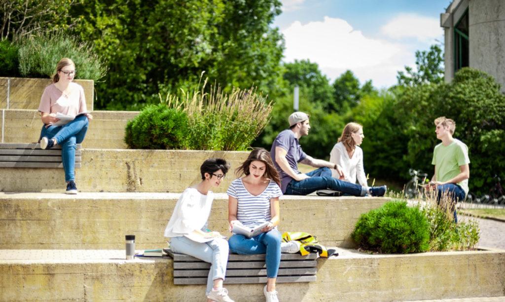 Diverse Studierende sitzen in kleinen Grüppchen auf begrünten Stufen eines Campus