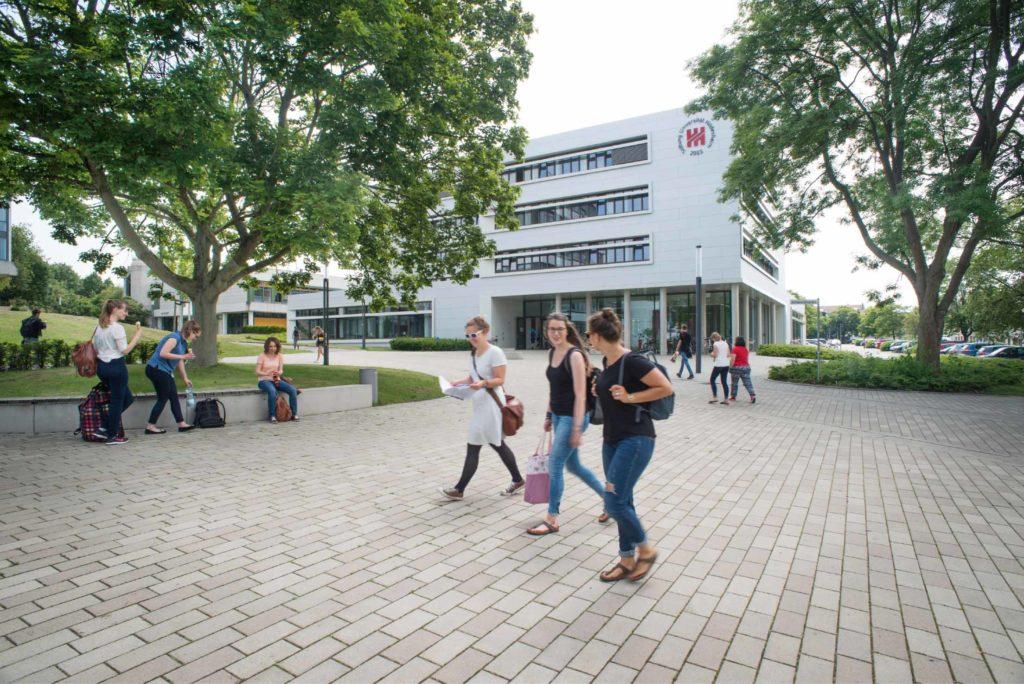Der Hauptcampus vor dem weißen Gebäude des Forums mit sommerlich gekleideten Studierenden, die sich unterhalten.