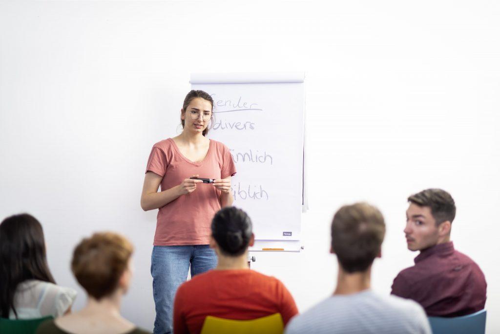 Eine Frau steht vor einer Gruppe sitzender Menschen. Hinter ihr ist Flichart. In iher Hand hält sie einen Edding.