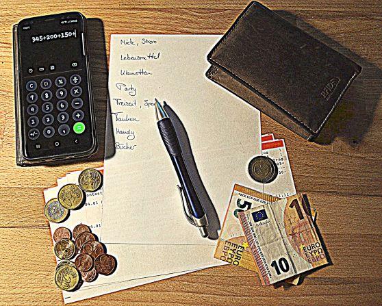 Auf einer Tischplatte liegt eine Liste mit verschiedenen Ausgaben: Miete, Strom, Lebensmittel, Klamotten, Party, Freizeit, Sport, Tanken, Handy, Bücher. Auf der Liste liegt ein Kugelschreiber. Um die Lieste herum liegen: ein Protominae, verschiedene Münzen und Geldscheine, ein Handy auf dem der Taschenrechner offen ist. Unter der Liste, den Münzen und den Scheinen sind Kontoauszüge zu erkennen.