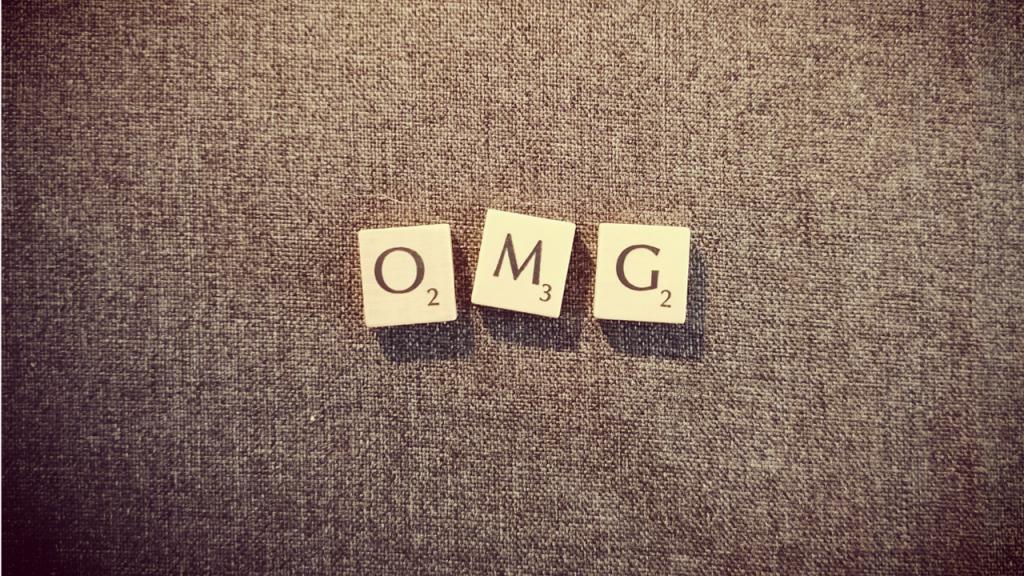 """Fotografie von Holzklötzchen aus dem Spiel Scrabble mit den Buchstaben """"O"""", """"M"""" und """"G"""" auf grauem Hintergrund"""