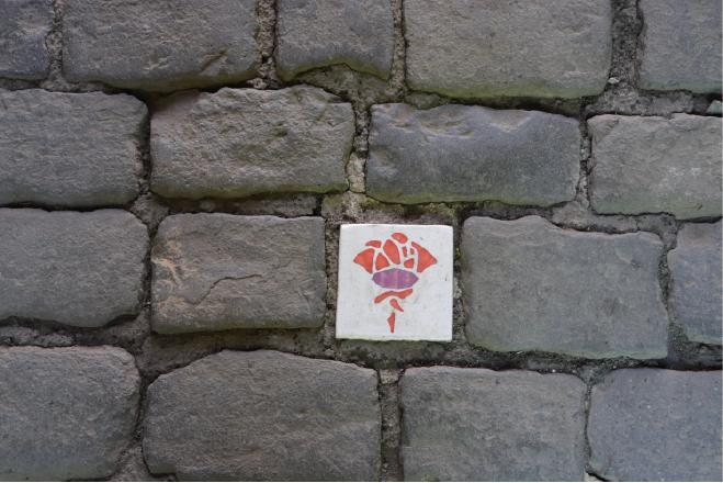 Fotografie des Straßenpflasters, in dem ein Pflasterstein in weiß eine rote Rose abbildet.