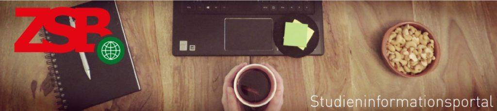 Schreibblock, Laptop, eine Schüssel mit Nüssen und Hände, die eine Tasse Kaffe umschließen auf einem Tisch