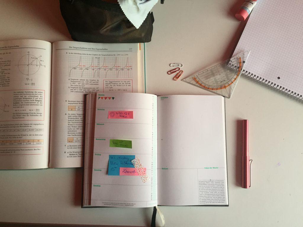 Eine weiße Fläche, darauf ein aufgeschlagener Kalender, in welchem die Lehramtsinformationsveranstaltung markiert ist. Außerdem ein aufgeschlagenes Matheschulbuch, Büroklammern, ein Geodreieck, ein Füller, verschiedenes Schreibmaterial am Rand des Fotos.