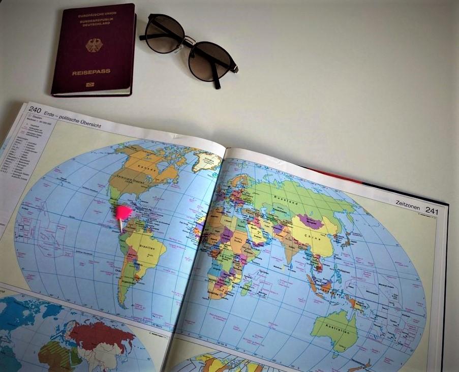 Ein aufgeschlagener Atlas mit bunter Weltkarte und einem pinken Fähnchen auf der Fläche von Ecuador. Über dem Atlas liegen ein roter europäischer Reisepass und eine braune runde Sonnenbrille.