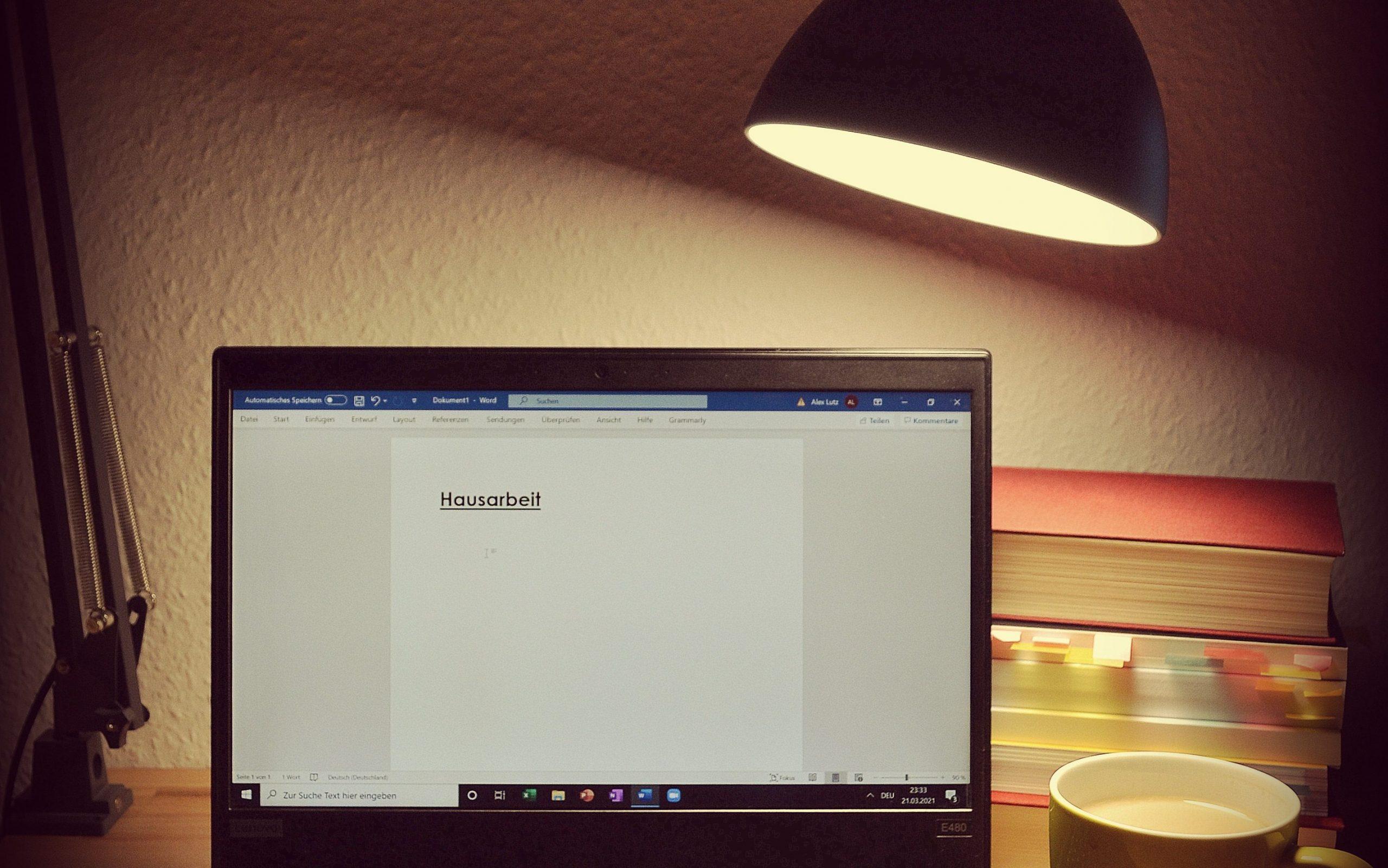 Ein schwarzer Laptop, der von einer Schreibtischlampe angeleuchtet wird. Auf dem Laptop ist ein Word-Dokument offen. Bis auf die Überschrift Hausarbeit ist die Seite noch leer. Rechts vom Laptop ist eine volle Kaffeetasse zu erkennen. Rechts hinter dem Laptop befindet sich ein Stapel mit Büchern.