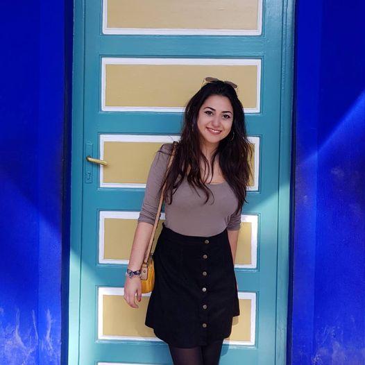 Ein Foto von Eda vor einer blau-gelben Tür