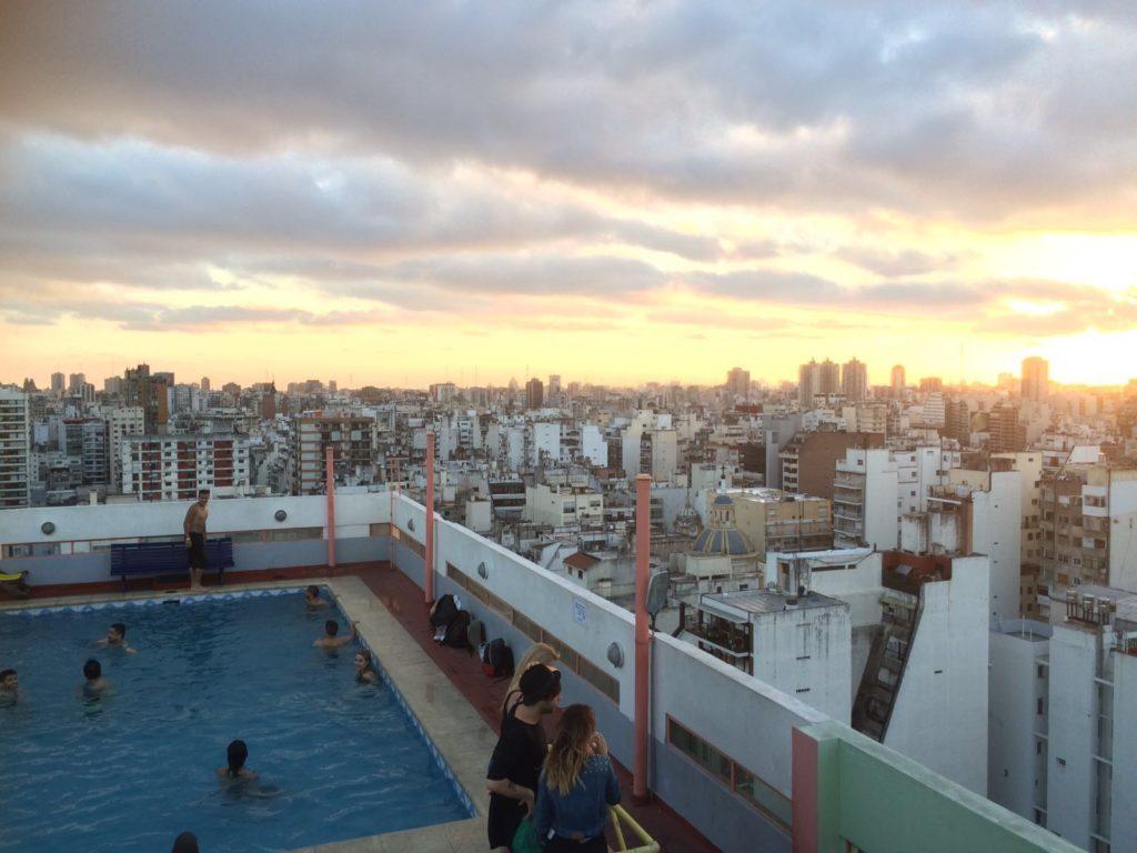 Blick über Buenos Aires mit Sonnenuntergang von einer Dachterasse mit Pool. Menschen befinden sich im Pool oder um diesen herum.